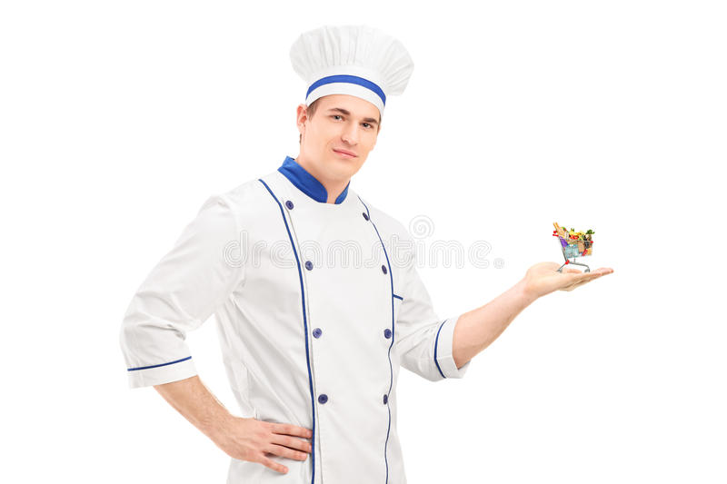 Male chef holding a small shopping cart with food products stock photo