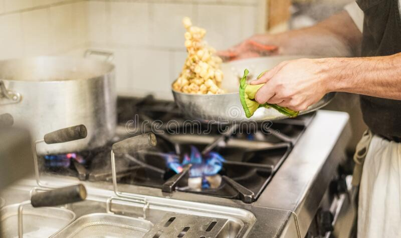 Male chef mixing with sauce fresh homemade pasta in restaurant kitchen - Bearded cook at work during dinner service - Italian. Style cuisine, lifestyle and stock photos