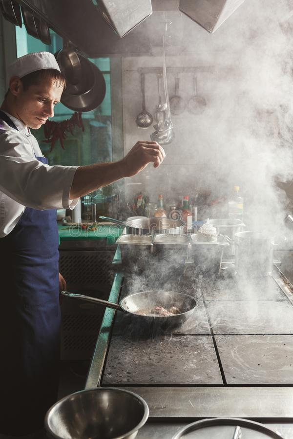 Chef cooking meat at restaurant or hotel kitchen royalty free stock images