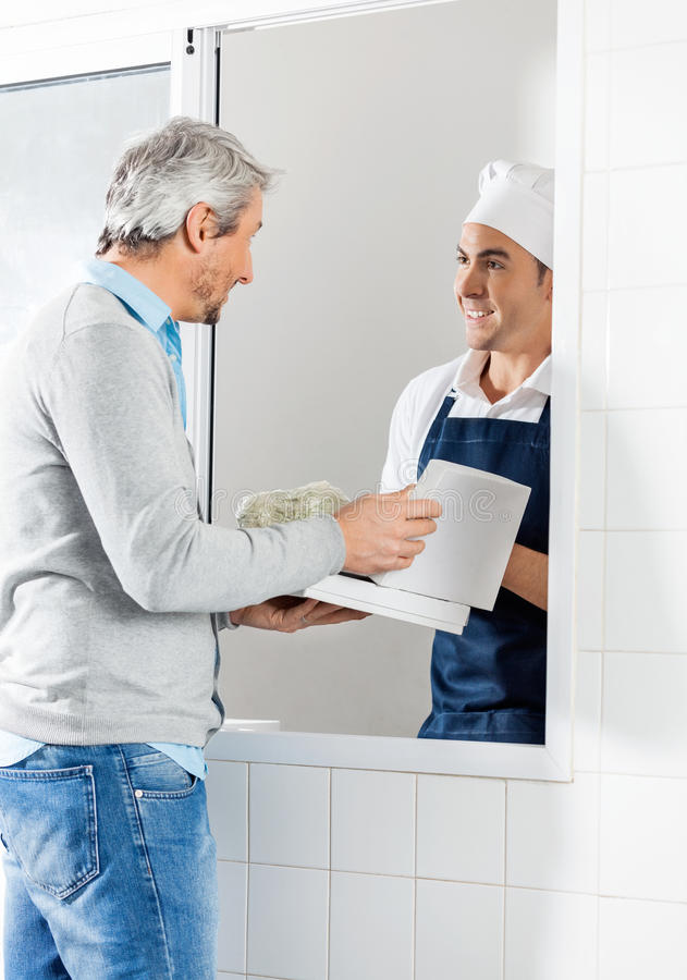 Male Chef Selling Pasta Packets To Man stock photography