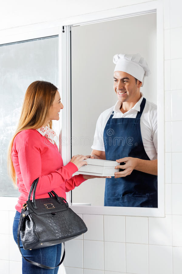 Male Chef Selling Pasta Packets To Woman royalty free stock photo