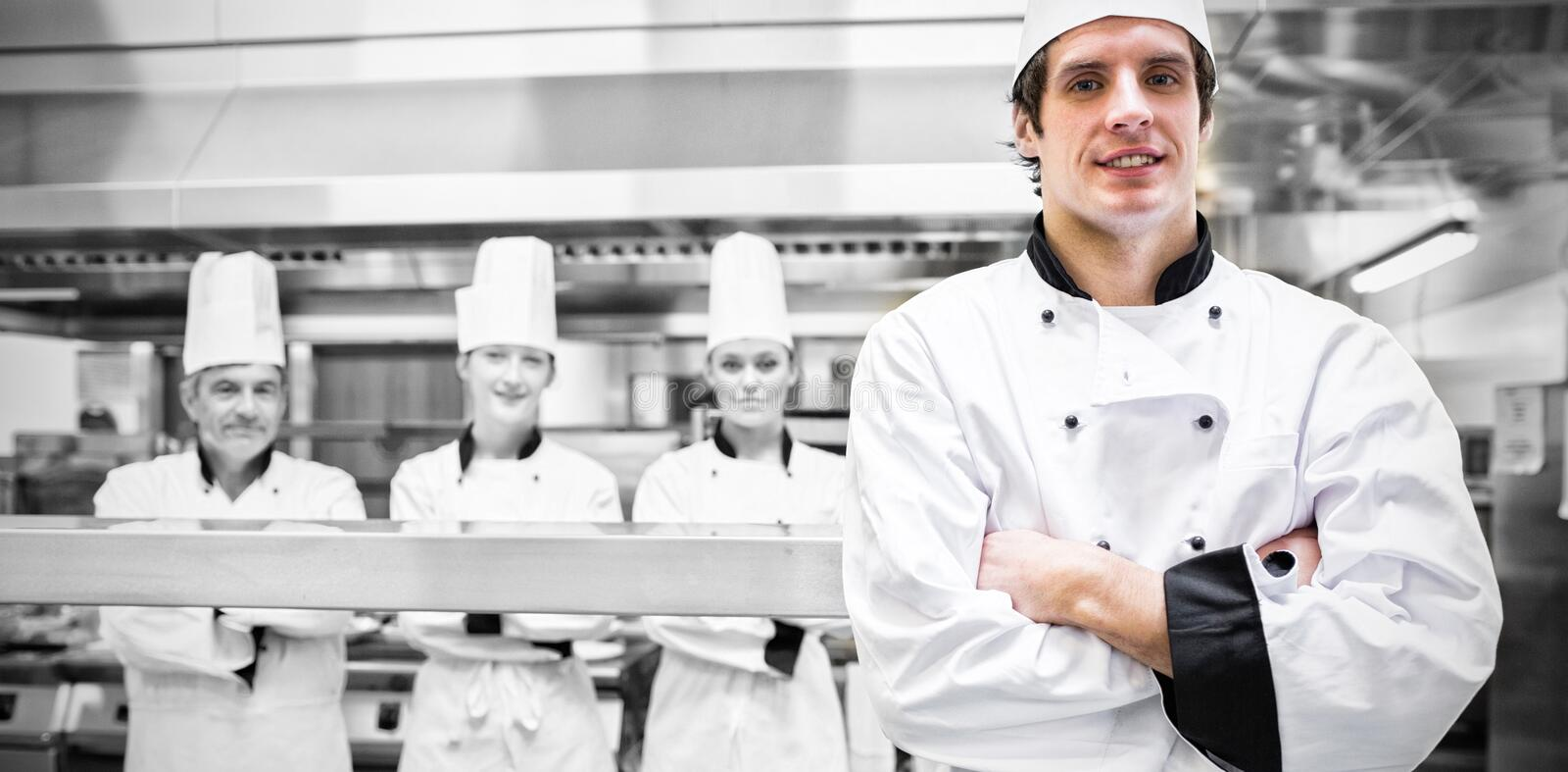 Male chef standing in kitchen. With team behind him stock photo