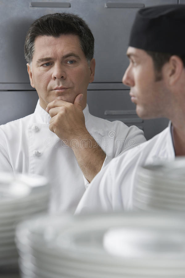 Male Chef Supervising Trainee In Kitchen. Closeup of a middle aged chef supervising trainee in the kitchen stock images