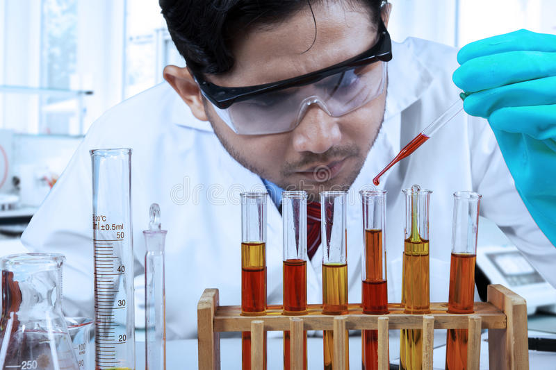 Male chemist pouring chemical fluid. Young pharmacy student doing experiment with chemical fluid and test tube stock images