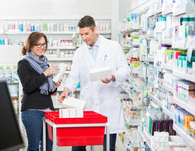 Male Chemist Showing Medicines To Female Customer royalty free stock photo