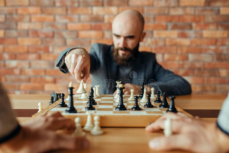 Male chess player with white figure in hand. Queen move. Chessplayer at board, front view, intellectual tournament indoors. Chessboard on wooden table stock photography
