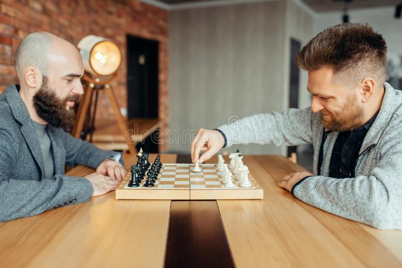 Male chess players begin playing, the first move stock photography