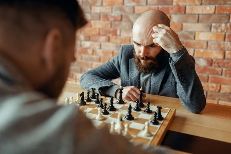 Male chess players playing, thinking process royalty free stock photo
