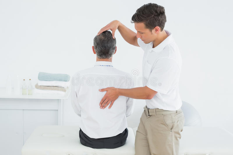 Male chiropractor examining mature man royalty free stock image