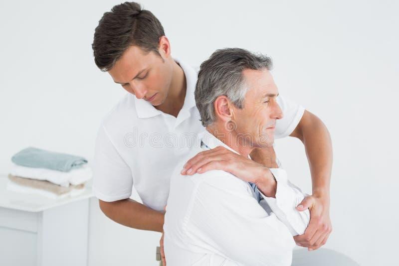 Male chiropractor examining mature man stock photos