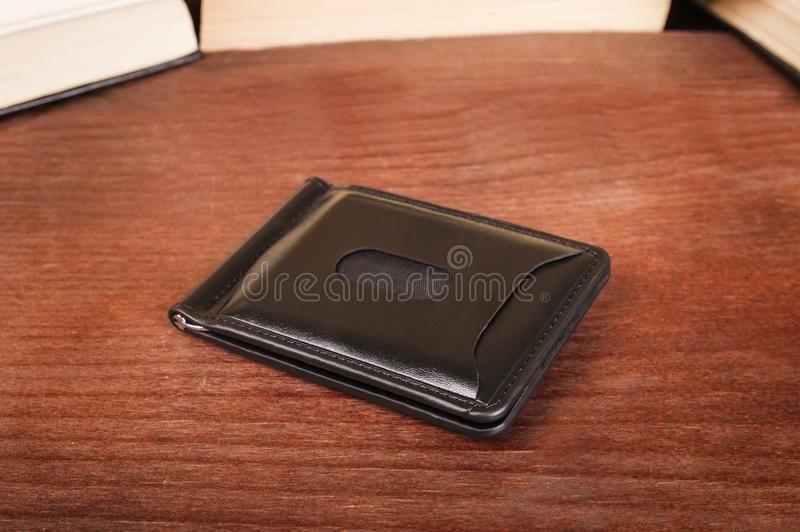 Male clamp for money. Closed leather wallet on a wooden background royalty free stock photos
