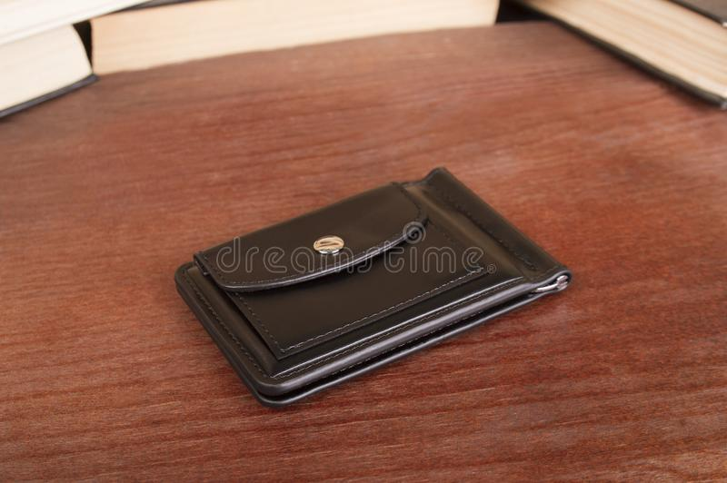 Male clamp for money. Closed leather wallet on a wooden background stock images