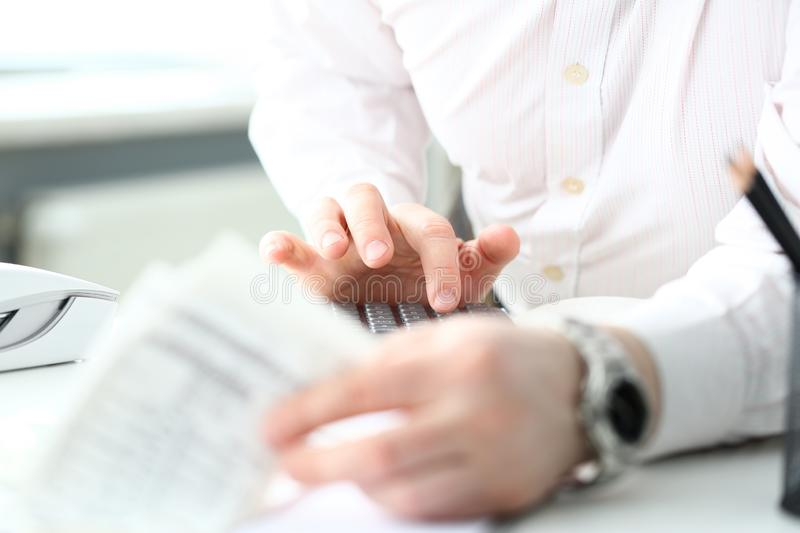 Male clerk finger pressing buttons on calculator devise evaluating expenses. Closeup stock photos