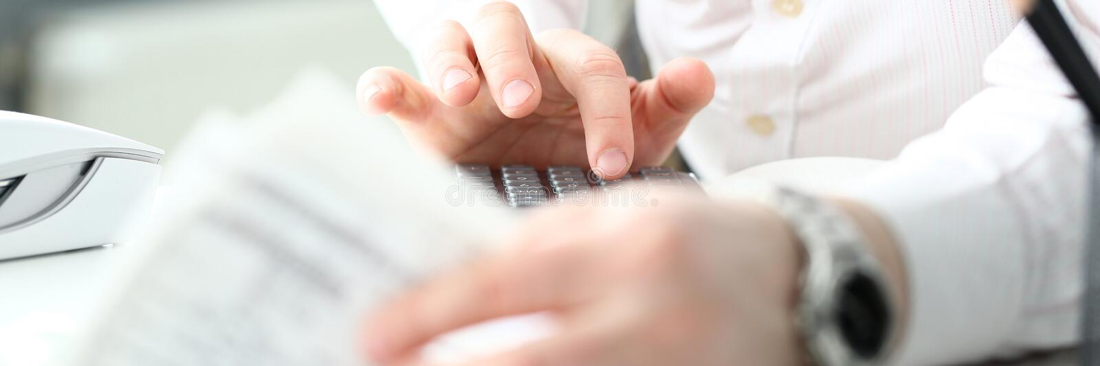 Male clerk finger pressing buttons on calculator devise evaluating expenses. Closeup royalty free stock photo