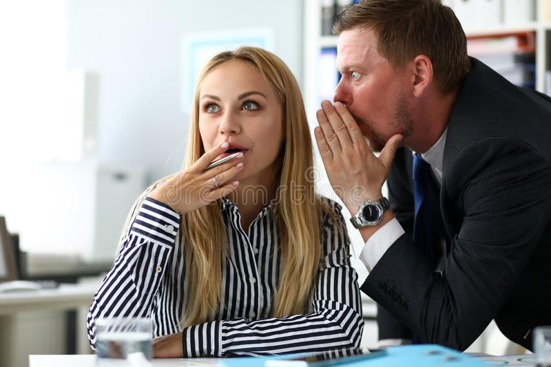 Male clerk sharing some secret knowledge with female colleague stock photo