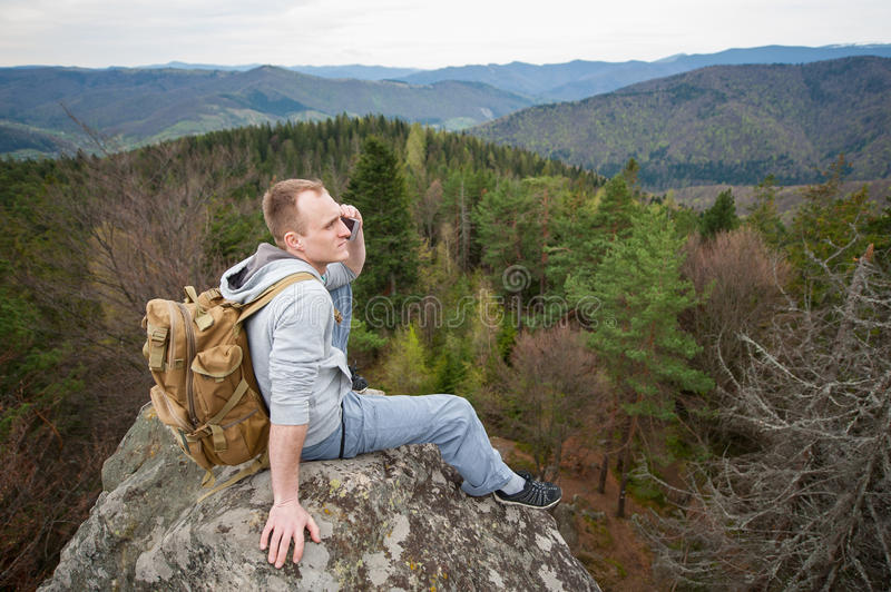 Male climber with brown backpack on the peak of rock. Male backpacker with a backpack is relaxing on the top of rock, looking away and talking on the phone on stock photo