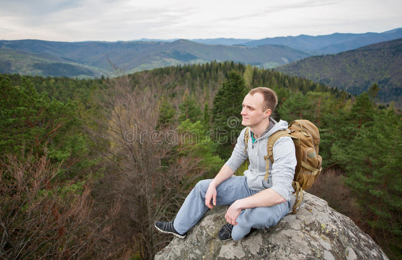 Male climber with brown backpack on the peak of rock. Backpacker sit and relax on the peak of rock and watching away on background of forest valley and hills stock photo