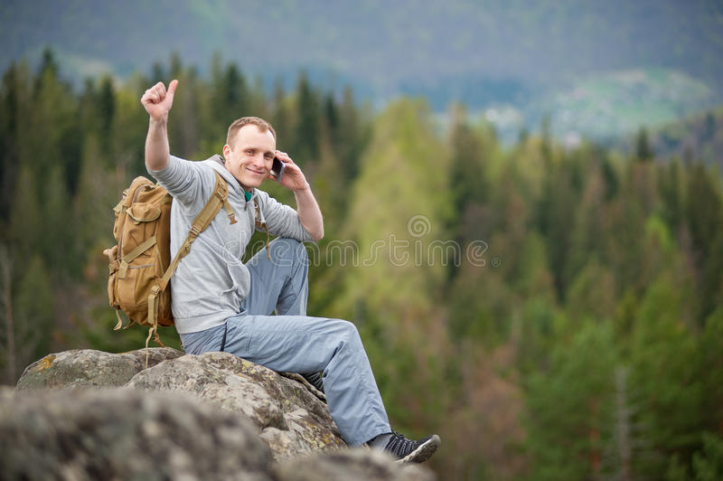 Male climber with brown backpack on the peak of rock. Happy tourist male with a brown backpack sitting on the peak of rock, talking on the phone and showing stock photography
