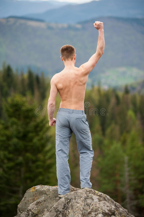 Male climber with brown backpack on the peak of rock. Man with a bare torso standing on the peak of a rock, with back to the camera with hands up, against stock photography