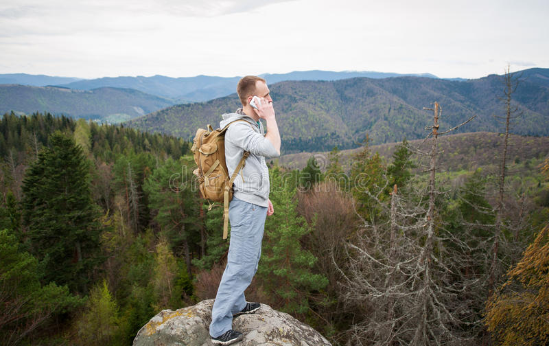 Male climber with brown backpack on the peak of rock. Tourist with brown backpack standing on the peak of a rock, with back to the camera, talking on the phone stock images