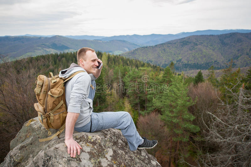 Male climber with brown backpack on the peak of rock. Young brave man with a backpack sitting on the peak of rock, looking away and talking on the phone on the royalty free stock images