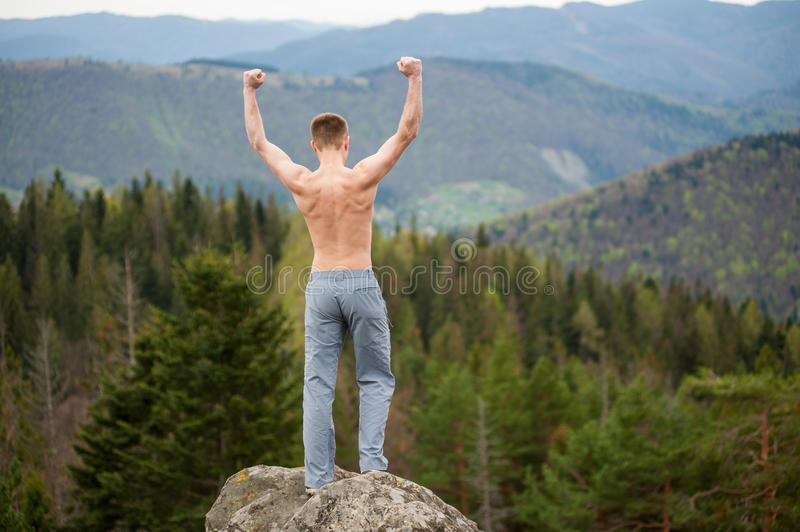 Male climber with brown backpack on the peak of rock. Young winner male with a bare torso standing on the peak of a rock, with back to the camera with hands up royalty free stock photo