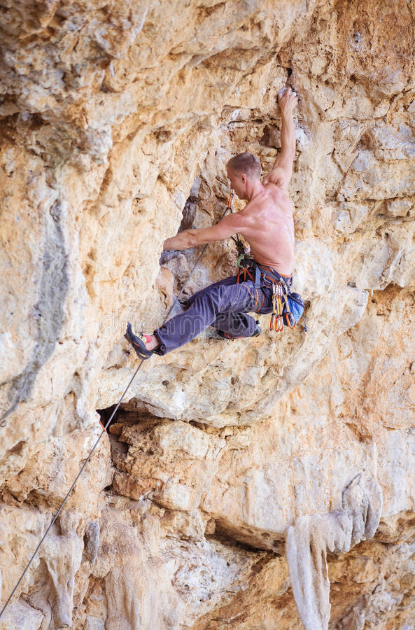 Male climber jumping on handholds stock photography