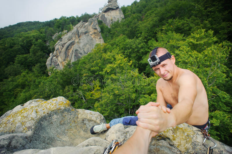 Male climber is reaching for a helping-hand from his partner stock image