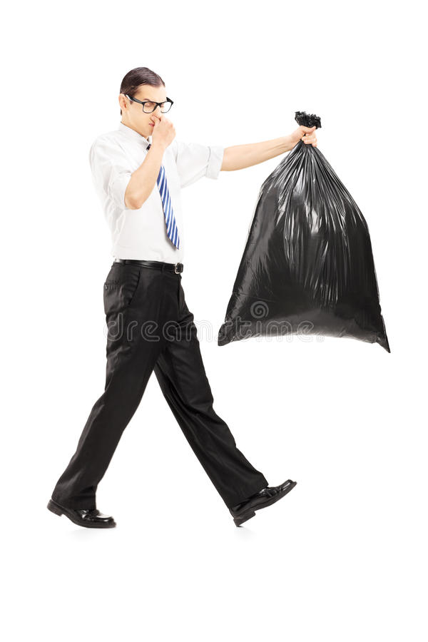 Download Male Closing His Nose And Carrying A Stinky Garbage Bag Stock Photo - Image: 34660034