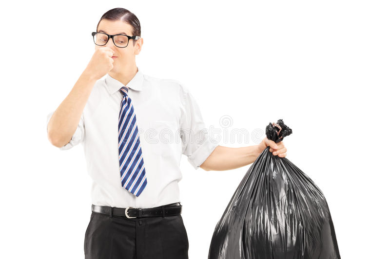 Male Closing His Nose And Holding A Stinky Garbage Bag Stock Photos