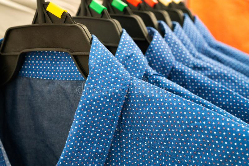 Male cloth, row of blue man shirts on hanger in closet royalty free stock photos