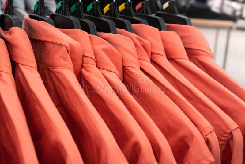 Male cloth, row of red man shirts on hanger in closet stock images