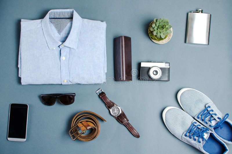 Male clothes and fashion accessories flatlay. Male clothes and fashion accessories on blue background flatlay royalty free stock photography
