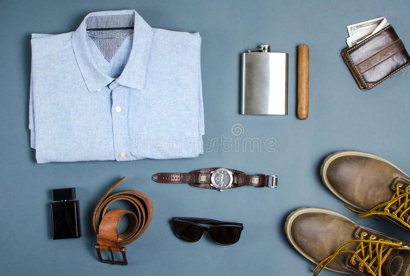 Male clothes and fashion accessories flatlay. Male clothes and fashion accessories on blue background flatlay royalty free stock image