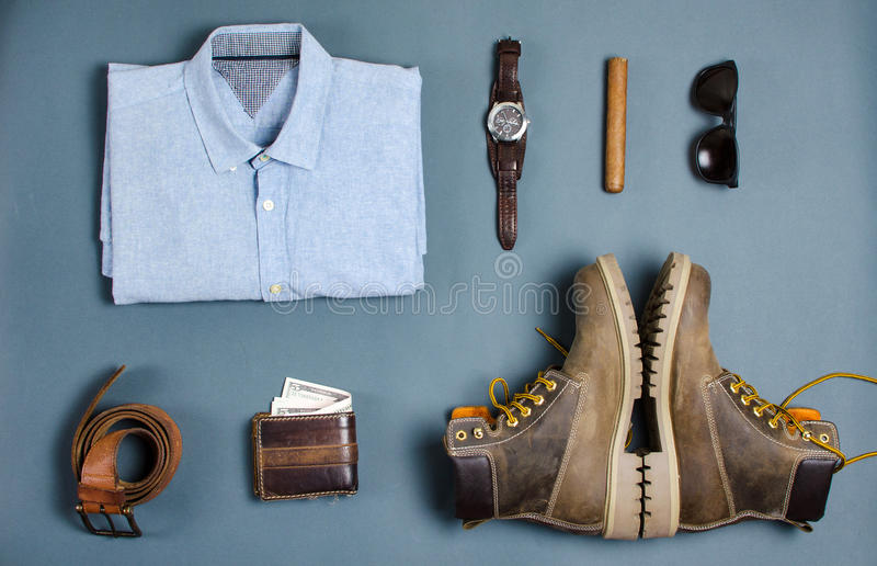 Male clothes and fashion accessories flatlay. Male clothes and fashion accessories on blue background flatlay royalty free stock images