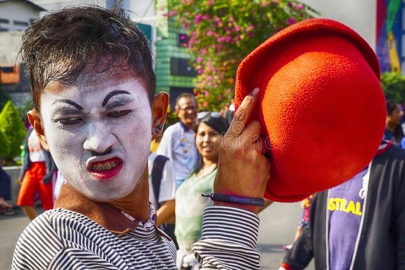 Street clown is in action on his stage, the street. A male clown with his funny facial expressions perform in the street while people passing by are attracted royalty free stock photo