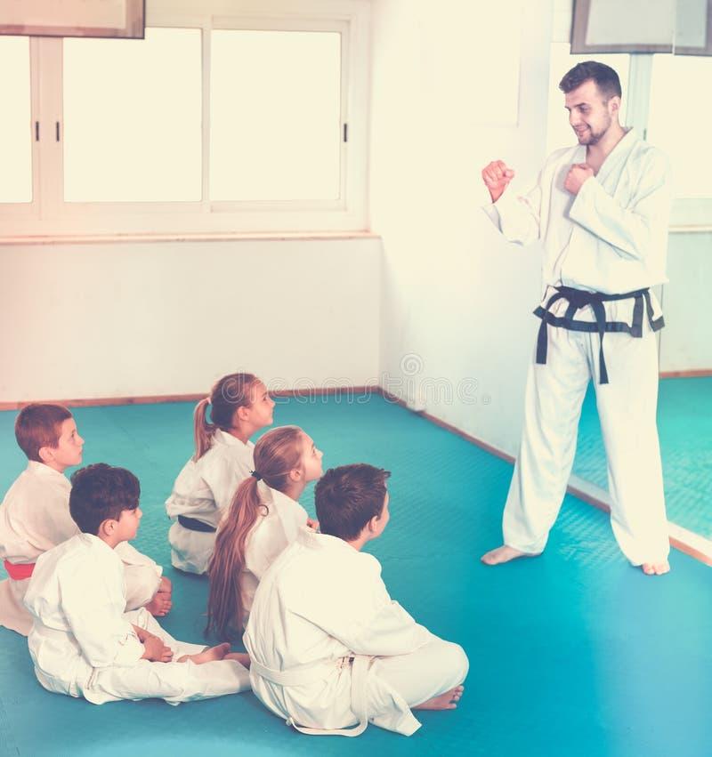 Male coach explaining new maneuvers to children stock image