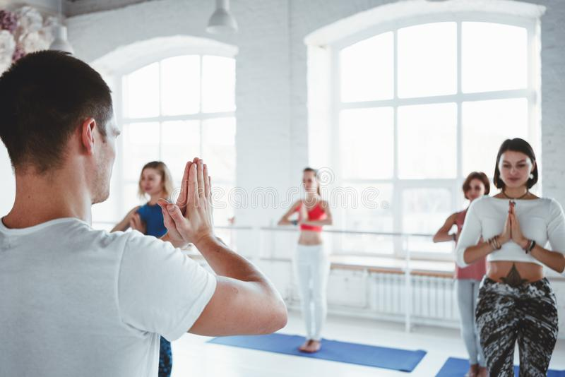 Male coach practice yoga exercise with woman group indoor gym. Together fit training. Woman health care. Male coach practice yoga exercise with women group royalty free stock images