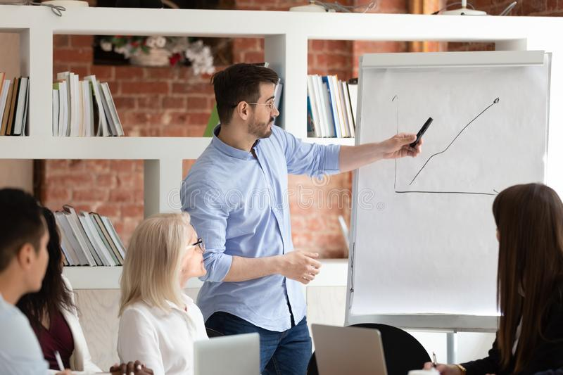 Male coach talk making flipchart presentation for staff. Millennial male coach stand make whiteboard presentation show graph training diverse coworkers, men stock image