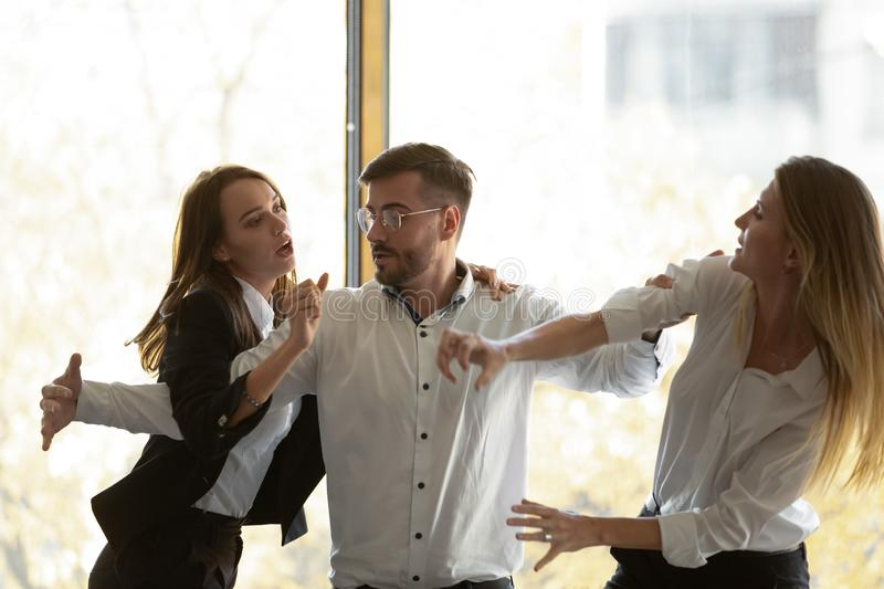 Male colleague set apart aggressive business women fighting in office royalty free stock image
