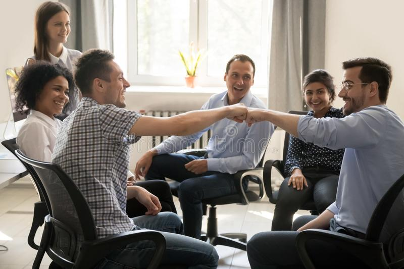 Male colleagues fist bumping at group meeting celebrating good t. Eamwork results concept, happy smiling team office workers sharing success motivated by great stock photography