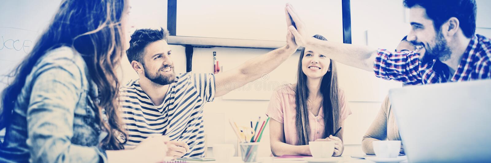 Male colleagues giving high-five in meeting at creative office stock photo