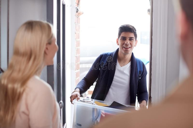 Male College Student Carrying Box Moving Into Accommodation Meeting House Mates royalty free stock photography