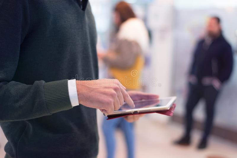 Male college student standing in corridor of university after her class and holding his tablet stock photo