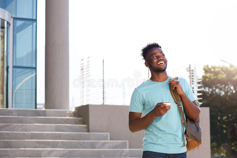 Male college student walking by stairs with bag and smart phone. Portrait of male college student walking by stairs with bag and smart phone royalty free stock photos