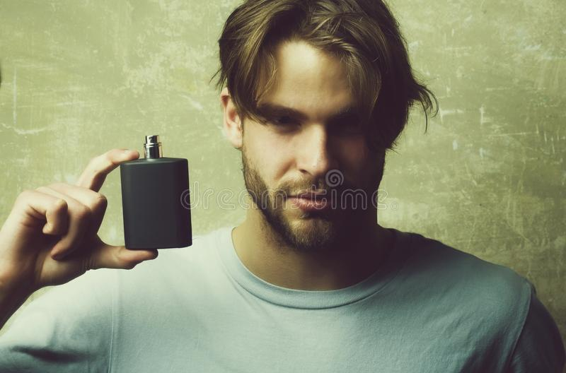 Male cologne. guy with black perfume bottle royalty free stock photo
