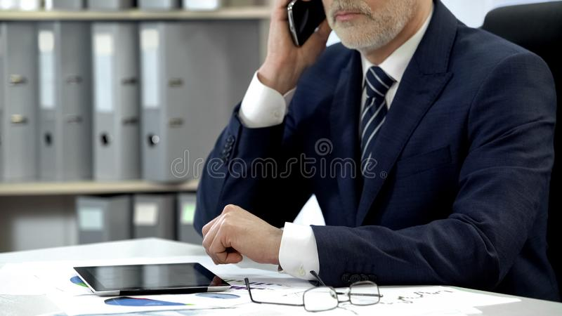 Male company director dialing, talking cell phone, tablet and glasses on table stock photo