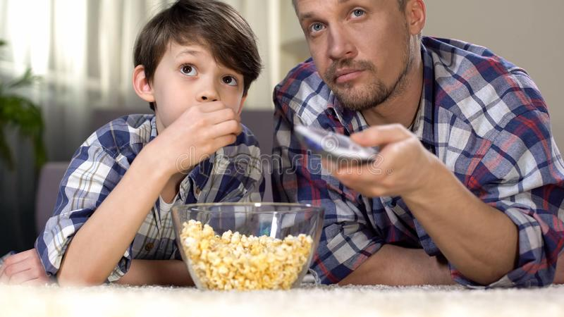 Male company spending time together watching tv and eating popcorn, fatherhood royalty free stock photo
