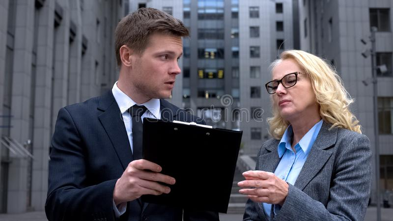 Male company worker discussing contract details with mature female colleague royalty free stock photo