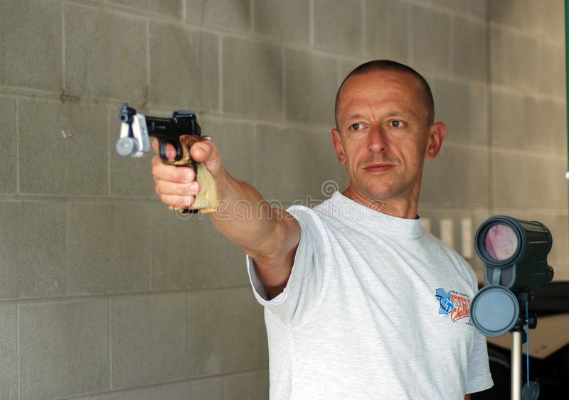 Male competitor at shooting range. Aiming to shooting stock photography